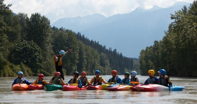 Athletes and volunteers goof around while kayaking on the Lillooet River in Pemberton